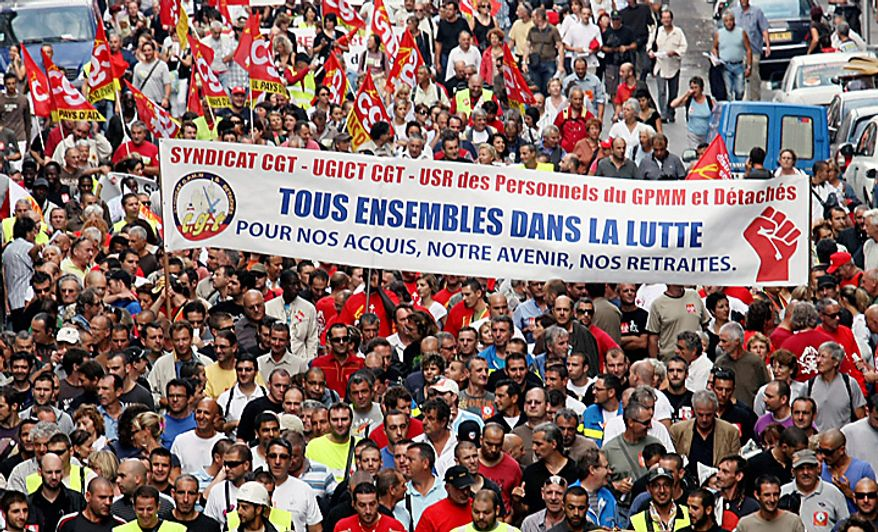 "** FILE ** Protesters march in Marseille, France, on Tuesday, Sept. 7, 2010, to demonstrate against plans by President Nicolas Sarkozy's government to raise the retirement age from 60 to 62. The banner reads: ""Fighting Together. For what we got, our future, our pension."" (AP Photo/Claude Paris)"