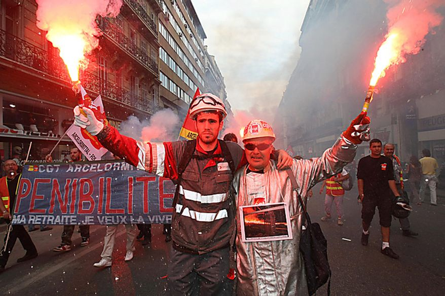 Workers march with flares during a protest, in Marseille, southern France, Tuesday Sept. 7, 2010. More than 200 street demonstrations were scheduled throughout France during the one-day movement. Civil aviation authorities asked airlines to cut a quarter of flights at Paris' airports, only two out of five fast trains are scheduled to run, and traffic was slowed on Paris' subway and suburban transport lines . (AP Photo/Claude Paris)