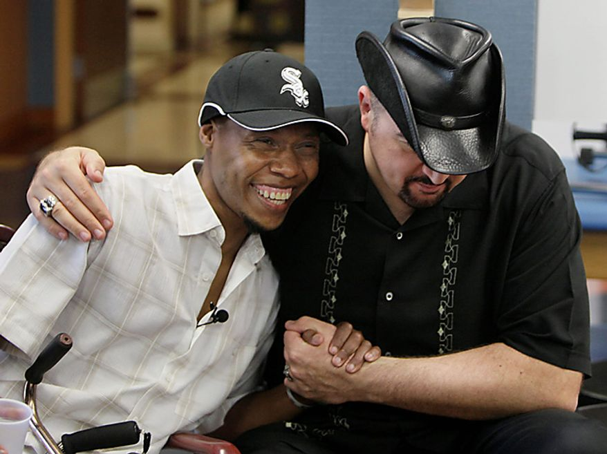 In this photo taken June 22, 2010, Bazelais Suy, left, and Dr. Dan Ivankovich hug after Suy's rehab session at Glencrest Nursing & Rehabilitation Centre in Chicago. Suy is a Haitian student activist whose spine was crushed when a university building collapsed in Haiti's catastrophic earthquake last January. He was airlifted to Chicago for six months of intensive rehabilitation and recently returned to Haiti with hopes of helping rebuild the country. (AP Photo/M. Spencer Green)