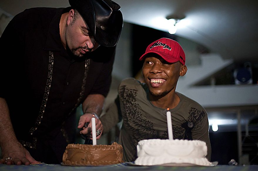 In this July 6, 2010 photo, Dr. Dan Ivankovich, left, helps his patient Bazelais Suy blow out the candles during Suy's birthday party Port-au-Prince, Haiti. Suy is a student activist whose spine was crushed when a university building collapsed in Haiti's catastrophic earthquake last January. He was airlifted to Chicago for six months of intensive rehabilitation and returned to Haiti with hopes of helping rebuild the country. (AP Photo/Ramon Espinosa)