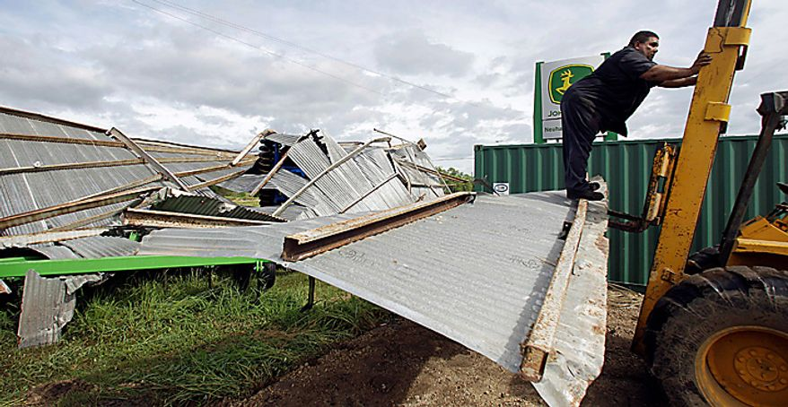 Workers clean up a pile of debris from a collapsed metal building, Tuesday, Sept. 7, 2010 in Raymondville, Texas, after Tropical storm Hermine swept through the area. (AP Photo/Eric Gay)