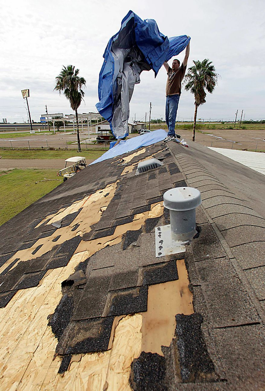 David Anderson covers his damaged roof with a blue tarp, Tuesday, Sept. 7, 2010 in Raymondville, Texas, after tropical storm Hermine swept through the area. (AP Photo/Eric Gay)
