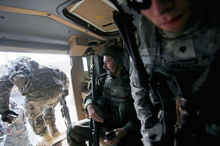 An Afghan army soldier and U.S. soldiers from the 2nd Battalion, 502 Infantry, 101st Airborne Division, prepare to exit an armored vehicle during a mission to Strongpoint Terminator, a jointly operated U.S.-Afghan base in Zhari district, Kandahar province, southern Afghanistan, last month. (Associated Press)
