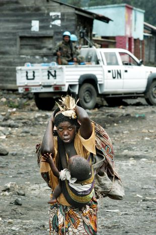 A Congolese woman laden with baggage and a young child walks past U.N. troops in Sake, Congo. (Associated Press)
