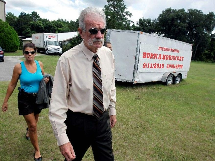 """Associated Press photographs Pastor Terry Jones, of the Dove World Outreach Center in Gainesville, Fla., arrives at a news conference with an armed escort Wednesday. Mr. Jones said of his plans to burn Korans on Saturday: """"It is possibly time for us in a new way to stand up and confront terrorism."""""""