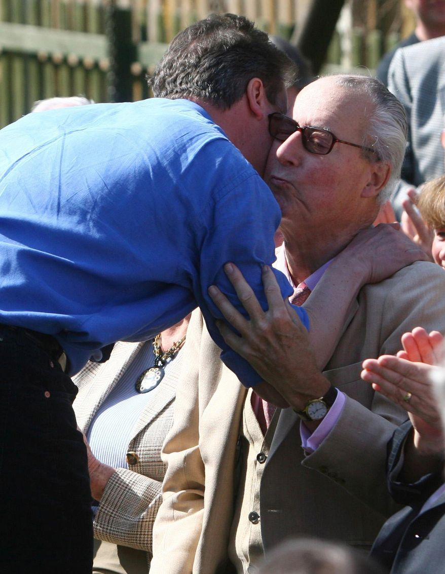 ** FILE ** David Cameron (left), now Great Britain's prime minister, greets his father, Ian, during a visit to the Sun Inn in Swindon, England, in March 2010. The elder Mr. Cameron suffered a stroke while on vacation in France and died on Wednesday. (AP Photo/Johnny Green/PA, File)