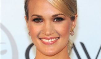 American singer Carrie Underwood is announced as the first ever North American spokesperson for Olay beauty products on Wednesday, Sept. 8, 2010 in New York. (AP Photo/Evan Agostini)
