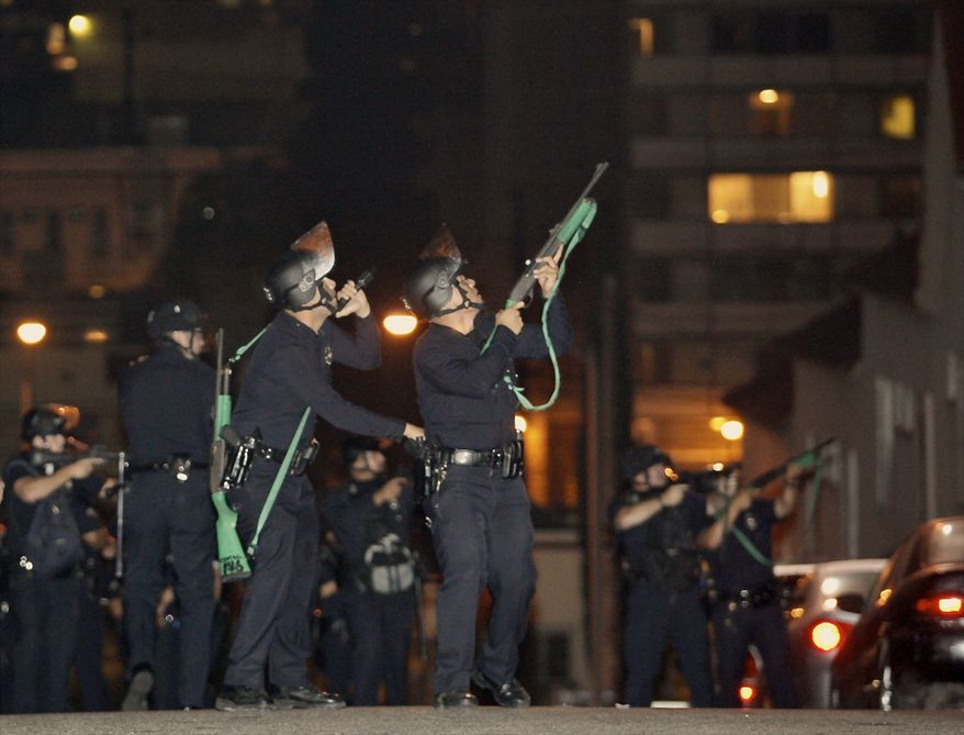 Los Angeles police fire nonlethal foam projectiles toward apartment building rooftops as protesters  throw such household items as air conditioners, furniture and televisions on the officers on Tuesday, Sept. 7, 2010, in response to the shooting death of a Guatemalan immigrant by police on Sunday. (AP Photo/Damian Dovarganes)