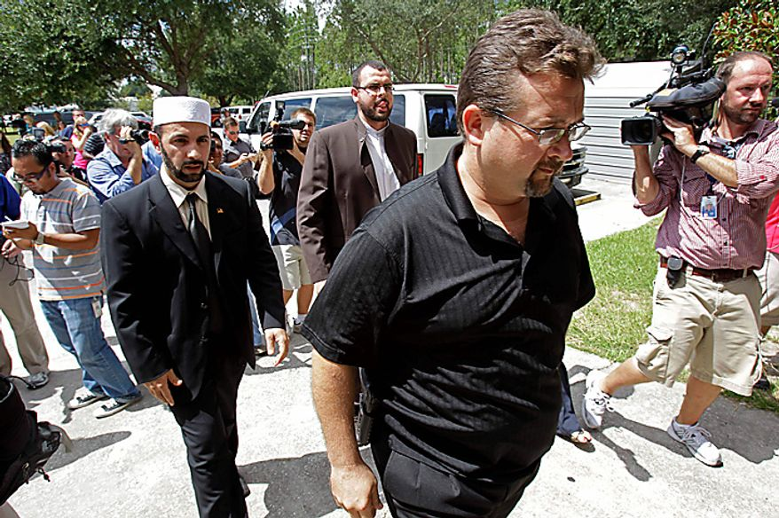 Wayne Sapp, right, an Associate Pastor of the Dove World Outreach Center, armed with a pistol on his hip, escorts Imam Muhammed Musri, left, President of the Islamic Society of Central Florida, in the church to meet with Pastor Terry Jones in  Gainesville, Fla., Wednesday, Sept. 8, 2010. Jones stated that he is going forward with a scheduled burning of copies of the Quran at his church on Saturday, Sept. 11. (AP Photo/John Raoux)