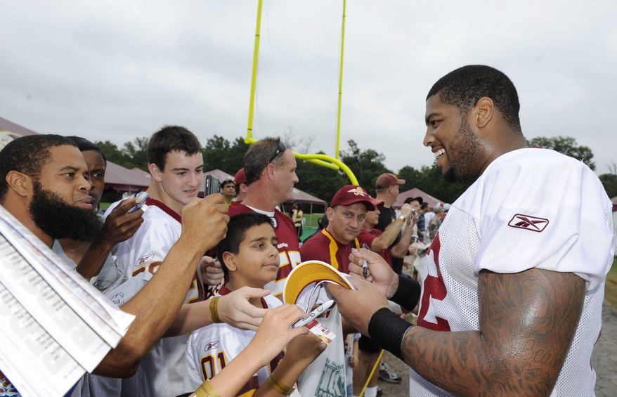 ASSOCIATED PRESS Washington Redskins offensive tackle Trent Williams, right, meets with fans after practice at the NFL football team's training camp, Sunday, Aug. 15, 2010, at Redskins Park in Ashburn, Va.