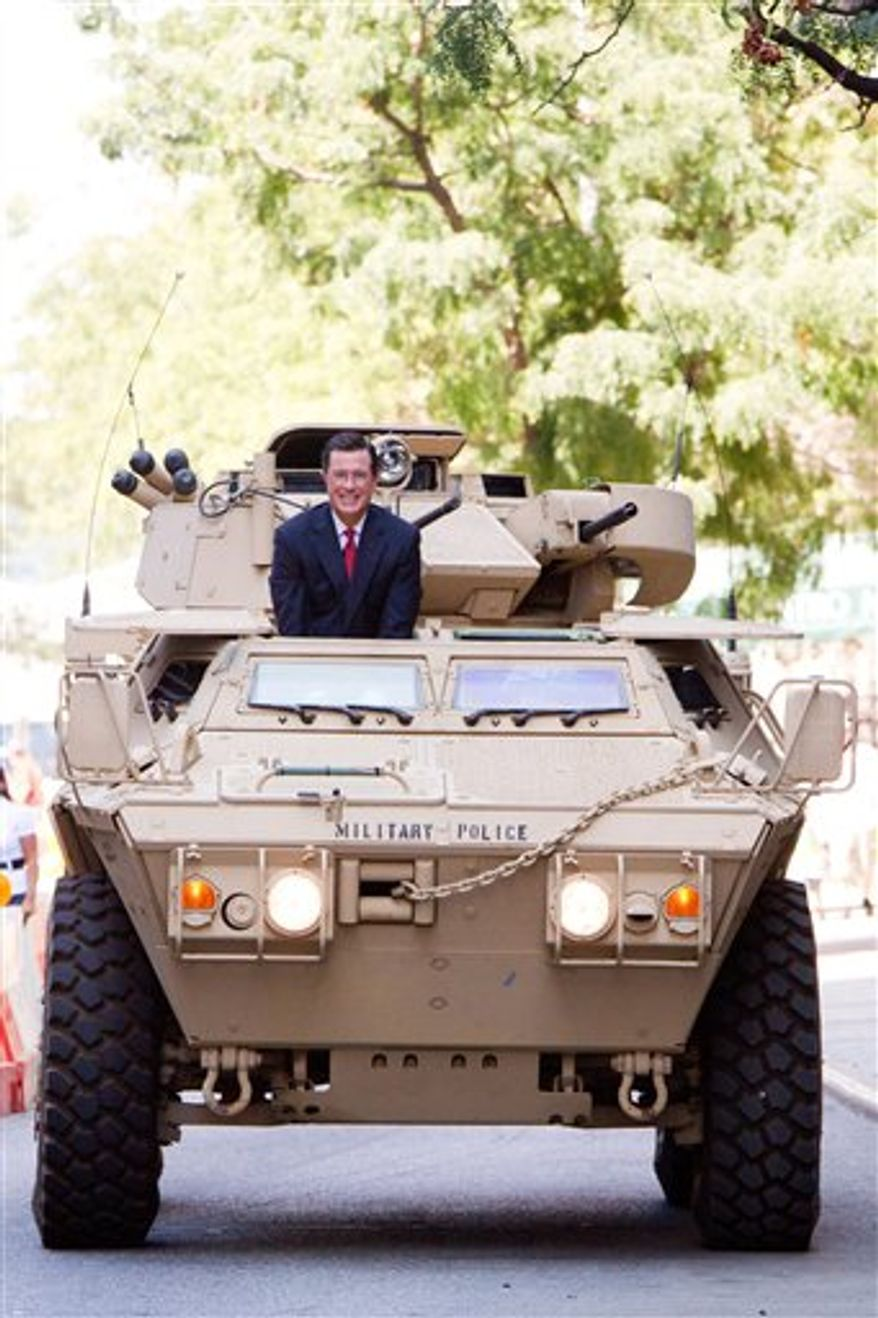Stephen Colbert rides an Army ASV while taping an episode of the Colbert Report on West 54th Street in New York, Wednesday, September 8, 2010. (AP Photo/Charles Sykes)
