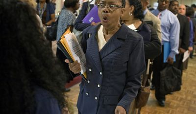 In this Aug. 24, 2010, photograph, Dabura Karriem, 60, of Bloomfield, N.J., reacts upon hearing there is a job availability for exactly what she's looking for as a file clerk at a bank, while attending a career fair in Newark, N.J. The Labor Department said jobless claims fell by 27,000 to 451,000 last week. (AP Photo/David Goldman)