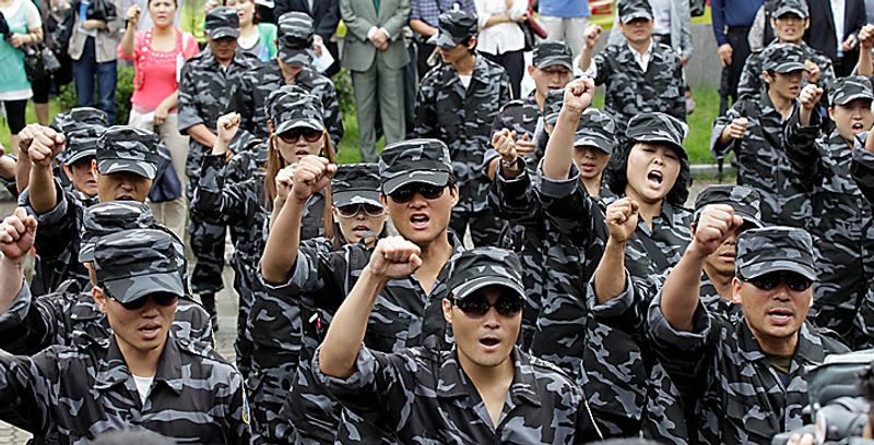 North Korean defectors wearing military uniforms shout slogans during the launching ceremony of the North Korea People Liberation Front, a group intend to fight against North Korea leader Kim Jong Il, in Seoul, South Korea, Thursday, Sept. 9, 2010. North Korea celebrated its 62nd anniversary Thursday with odes to supreme leader Kim Jong Il and pilgrimages to his late father's statue amid hints that a political meeting believed aimed at promoting his son as successor is imminent. (AP Photo/ Lee Jin-man)