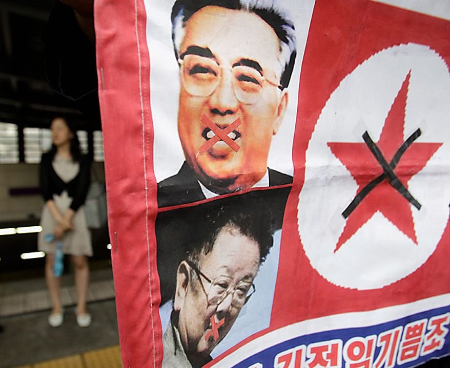 A woman walks by a North Korean flag attached with pictures of North Korean founder late Kim Il Sung, top, and his son, current North leader Kim Jong Il during a rally held against pro-North Korean groups in Seoul, South Korea, Thursday, Sept. 9, 2010. The youngest son of leader Kim Jong Il is widely expected to make his public debut as the Dear Leader's heir apparent at a rare Workers' Party convention, the nation's biggest political gathering in 30 years. (AP Photo/ Lee Jin-man)