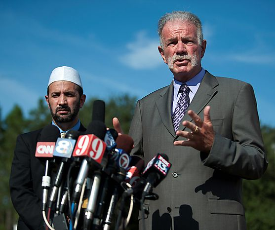 Pastor Terry Jones of the Dove World Outreach Center speaks to the media as Imam Muhammad Musri of the Islamic Society of Central Florida looks on at left, Thursday, Sept. 9, 2010, in Gainesville, Fla. (AP Photo/Phil Sandlin)