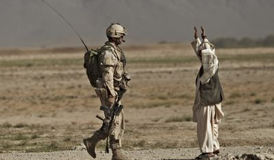 An Afghan man lifts up his arms as a Canadian soldier with the 1st RCR Battle Group, the Royal Canadian Regiment, approaches him during a patrol outside Salavat, in the Panjwaii district, southwest of Kandahar, Afghanistan, Thursday, Sept. 9, 2010. (AP Photo/Anja Niedringhaus)
