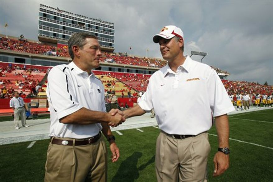 FILE - In this Sept. 12, 2009, file photo, Iowa coach Kirk Ferentz, left, greets Iowa State coach Paul Rhoads before an NCAA college football game in Ames, Iowa.  The rival coaches will meet for the second time on Saturday, and it looks as though they could be battling each other for years to come. (AP Photo/Charlie Neibergall, File)