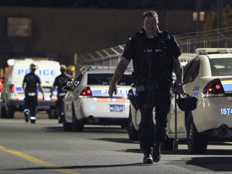 ** FILE ** A S.W.A.T. officer exits the scene of a workplace shooting at the Kraft Foods Inc. facility in Northeast Philadelphia on Sept. 9, 2010. (AP Photo/ Joseph Kaczmarek)