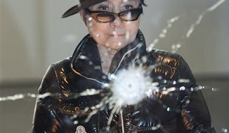 "Japanese artist Yoko Ono poses in her exhibition in Berlin, Germany, Friday, Sept.10, 2010. Yoko Ono seeks to draw viewers into her latest exhibition, ""Das Gift"" by asking for their participation in healing the world of violence, embodied by a bullet hole shot through a pane of glass through which viewers are invited to contemplate the space around them. (AP Photo/Gero Breloer)"