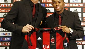 AC Milan newly signed soccer forwards Zlatan Ibrahimovic, of Sweden, left, and Robinho, of Brazil, show a team jersey during the official presentation in downtown Milan, Italy, Thursday, Sept 9, 2010. (AP Photo/Antonio Calanni)