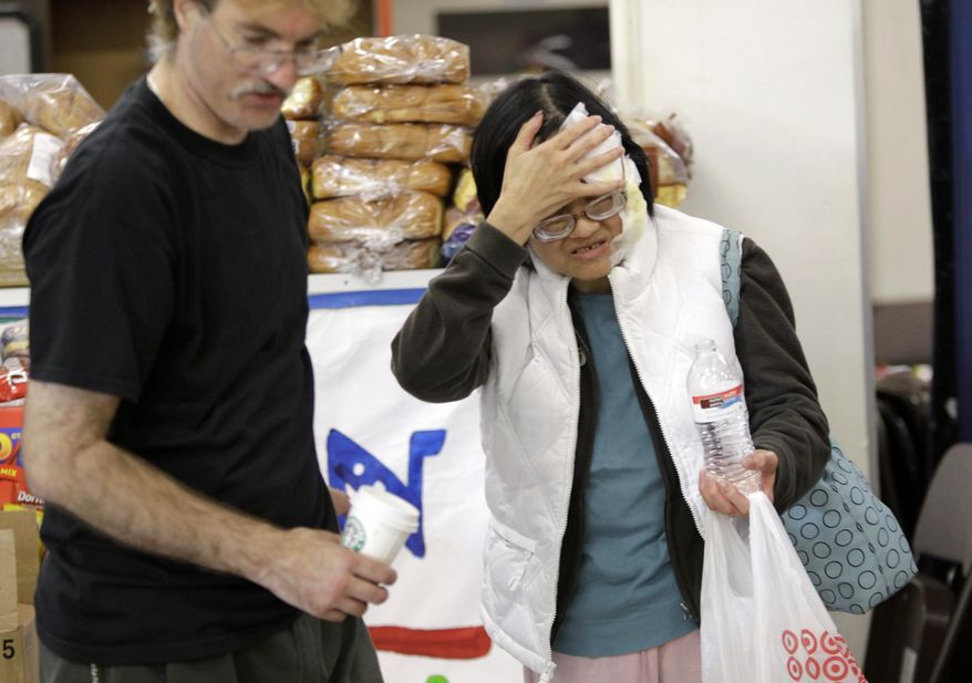 A volunteer, left, helps an evacuees who wished not to be identified, at a Red Cross shelter in San Bruno, Calif., Friday, Sept. 10, 2010, after she was injured at her home that burned down during a massive fire in her neighborhood on Thursday. According to officials, the massive explosion was apparently triggered by a broken gas line that sent flames roaring through a neighborhood near San Francisco. (AP Photo/Paul Sakuma)