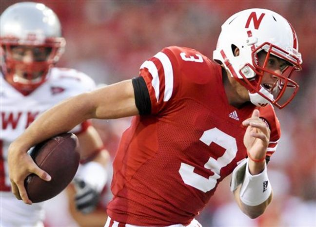 In a Saturday, Sept. 4, 2010, photo, Nebraska quarterback Taylor Martinez (3) runs for a touchdown during an NCAA college football game against Western Kentucky in Lincoln, Neb. It wasn't what Nebraska quarterbacks Zac Lee or Cody Green did wrong, it was what Martinez did right that earned the redshirt freshman the starting quarterback's job. Martinez did nothing to loosen his grip on it after running for 127 yards and three touchdowns in the Cornhuskers' season-opening win. (AP Photo/Dave Weaver)