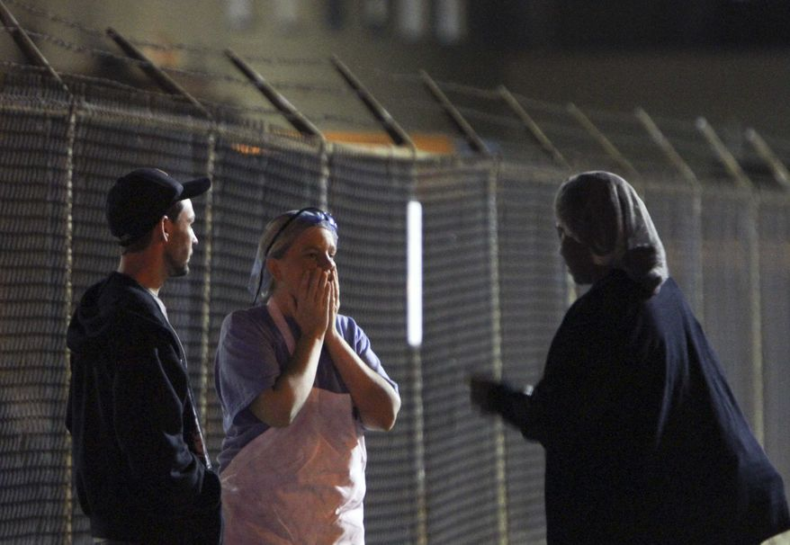 Unidentified employees talk outside the scene of a workplace shooting at the Kraft Foods Inc. facility in Northeast Philadelphia on Thursday, Sept. 9, 2010. (AP Photo/Joseph Kaczmarek)