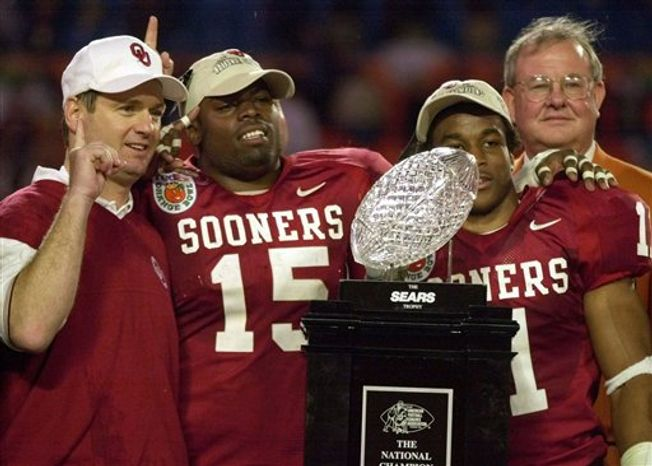 FILE - In this Jan. 3, 2001, file photo, Oklahoma coach Bob Stoops, left, celebrates with players J.T. Thatcher, (15) and Ontei Jones (11) as they pose with the trophy after beating Florida State 13-2 in the Orange Bowl NCAA college football game at Pro Player Stadium in Miami, Fla.  Trace the origins of Oklahoma's most recent rise to power,