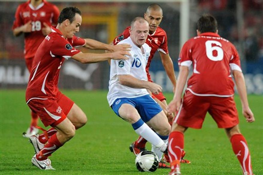 England's Wayne Rooney, center, scores  his side's first goal against Switzerland's goalkeeper Diego Benaglio, during the Euro 2012 group G qualification soccer match between Switzerland and England at the St. Jakob-Park Stadium in Basel, Switzerland, Tuesday, Sept. 7, 2010. (AP Photo/Keystone/Peter Klaunzer)