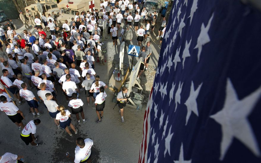 U.S. military personnel participate in the Patriot's Day 9.11 Kilometer Run, honoring those who lost their lives in the terrorist attacks of Sept. 11, 2001, at Bagram Air Field, Bagram, north of Kabul, Afghanistan, on Saturday, Sept. 11, 2010. (AP Photo/Mustafa Quraishi)