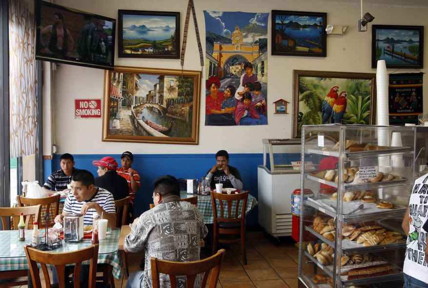Residents eat at a Guatemalan restaurant across the corner of Sixth Street and Union Avenue where police shot an illegal immigrant from Guatemala who was menacing officers with a knife, on Thursday, Sept. 9, 2010, in Los Angeles. (AP Photo/Damian Dovarganes)