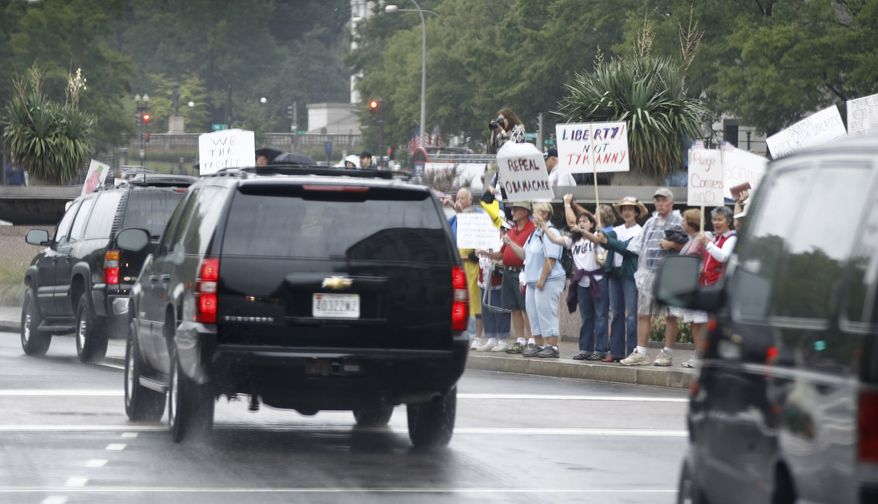 "President Obama's motorcade drives past ""tea party"" protesters on Pennsylvania Avenue Northwest as he returns to the White House from playing basketball at Fort McNair in Washington on Sunday, Sept. 12, 2010. (AP Photo/Charles Dharapak)"