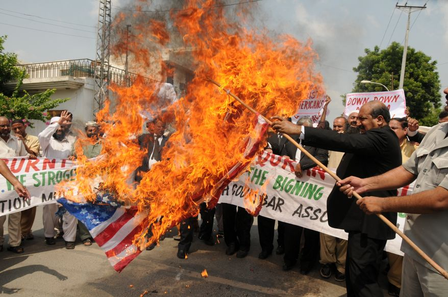**FILE** Pakistani lawyers burn a U.S. flag while rallying in reaction to a small American church's plan to burn copies of the Quran in Multan, Pakistan on Sept. 9, 2010. (Associated Press)