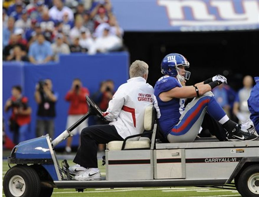 New York Giants' Kevin Boss, right, is taken off the field after being injured during the first quarter of an NFL football game against the Carolina Panthers at New Meadowlands Stadium in East Rutherford, N.J., Sunday, Sept. 12, 2010. Boss was hurt after being hit in the back of the neck by Panthers safety Sherrod Martin on the Giants' fourth play from scrimmage. (AP Photo/Henny Ray Abrams)