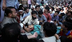 Kashmiri mourners surround the body of slain protester Nisar Ahmad Kuchay during his funeral on the outskirts of Srinagar, India, on Monday. Ongoing anti-India protests in the Muslim-majority region merged with outrage over a reported Koran desecration in the U.S. to spark violence. (Associated Press)