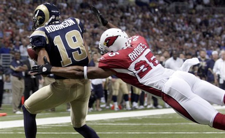 St. Louis Rams running back Steven Jackson, left, runs for an 8-yard gain past Arizona Cardinals defensive tackle Darnell Dockett, right, during the first quarter of an NFL football game Sunday, Sept. 12, 2010, in St. Louis. (AP Photo/Seth Perlman)