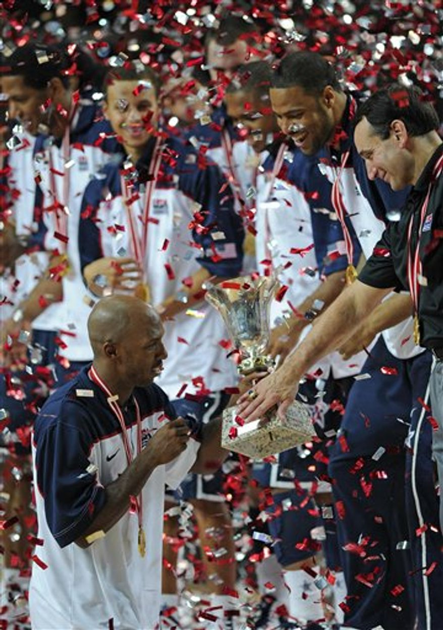 USA head coach Mike Krzyzewski, right, touches the base of the trophy held by USA's  Chauncey Billups after the final of the World Basketball Championship between Turkey and the USA, Sunday, Sept. 12, 2010, in Istanbul.  USA won the match 81-64.  (AP Photo/Mark J. Terrill)