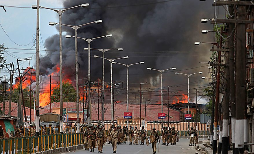 Indian forces patrol as flames rise from a government building set on fire by protesters in Srinagar, India, Saturday, Sept. 11, 2010. Police fired warning shots and tear gas to disperse hundreds of demonstrators who attacked a police post and burned government offices in Kashmir on Saturday, as tens of thousands of people took to the streets to protest Indian rule in the Himalayan region, officials said. (AP Photo/Altaf Qadri)