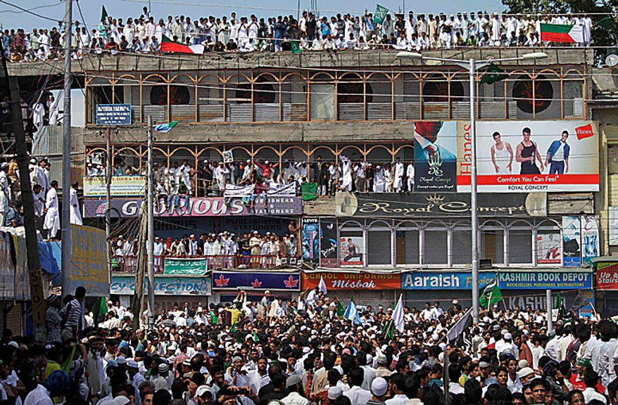 Kashmiri Muslim crowd rooftops and balconies as they participate in a protest rally after Eid al-Fitr prayers in Srinagar, India, Saturday, Sept. 11, 2010. Police fired warning shots and tear gas to disperse hundreds of demonstrators who attacked a police post and burned government offices in Kashmir on Saturday, as tens of thousands of people took to the streets to protest Indian rule in the Himalayan region, officials said. (AP Photo/Dar Yasin)