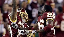 Washington Redskins cornerback DeAngelo Hall celebrates his touchdown with running back Clinton Portis after recovering a Dallas Cowboys running back Tashard Choice fumble during the first half of an NFL football game in Landover, Md., on Sunday, Sept. 12, 2010.  (AP Photo/Evan Vucci)