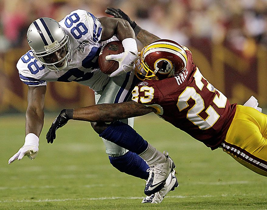 Dallas Cowboys wide receiver Dez Bryant is stopped by Washington Redskins cornerback DeAngelo Hall during the first half of an NFL football game in Landover, Md., on Sunday, Sept. 12, 2010. (AP Photo/Evan Vucci)