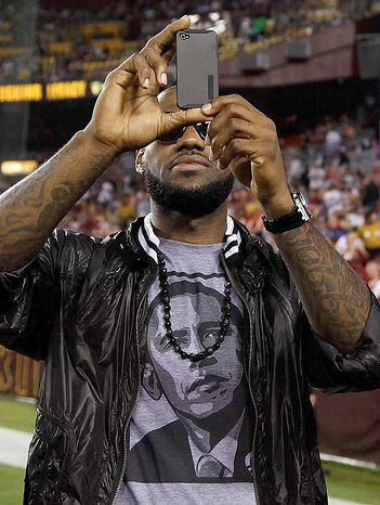 Basketball player LeBron James shoots a video with his cell phone from the sidelines before an NFL football game between the Dallas Cowboys and Washington Redskins in Landover, Md., on Sunday, Sept. 12, 2010.  (AP Photo/Evan Vucci)