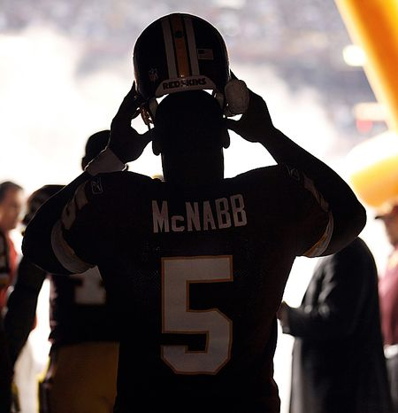 Washington Redskins quarterback Donovan McNabb pulls his helmet on in the tunnel before  an NFL football game against the Dallas Cowboys in Landover, Md., on Sunday, Sept. 12, 2010.  (AP Photo/Evan Vucci)
