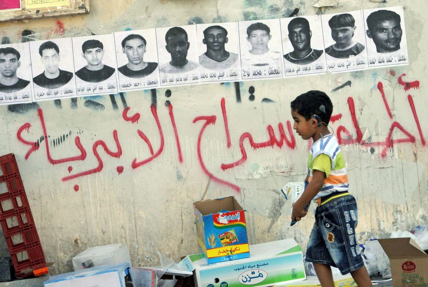 'FREE THE INNOCENT PEOPLE': A child passes by posters of detainees hanging on a wall in a village in Malkiya, Bahrain. Graffiti calls for their release. (Associated Press)
