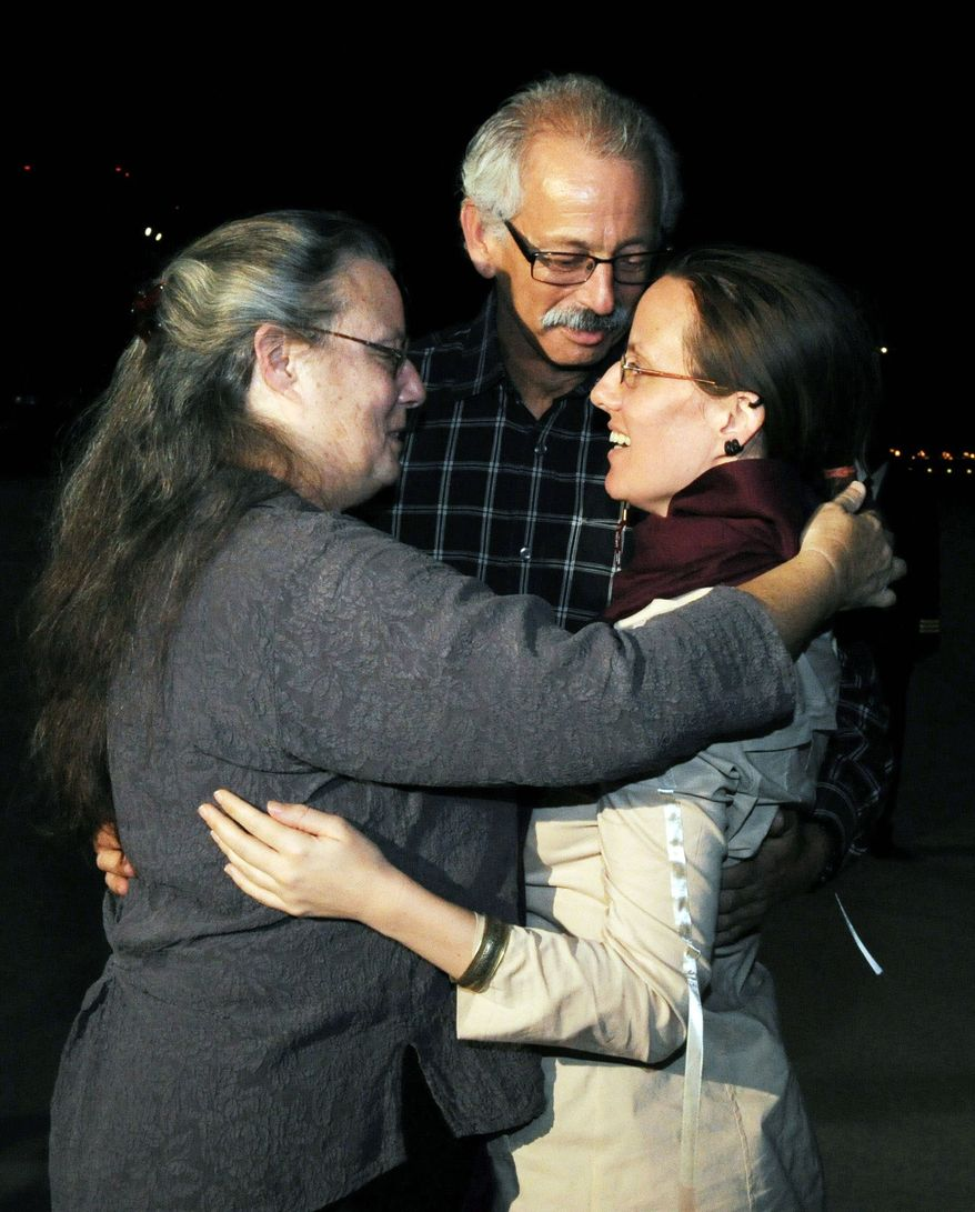 Sarah Shourd (right) embraces her mother, Nora Shourd, as an unidentified man looks on, during Sarah Shourd's arrival at the royal airport in Muscat, Oman, on Tuesday. (Associated Press)
