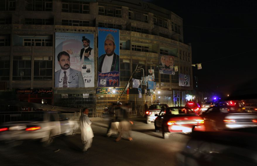 Afghans walk between traffic past posters of parliamentary candidates in Kabul, Afghanistan, Tuesday, Sept. 14, 2010. Fears of violence hang over Saturday's elections. (AP Photo/ Mustafa Quraishi)