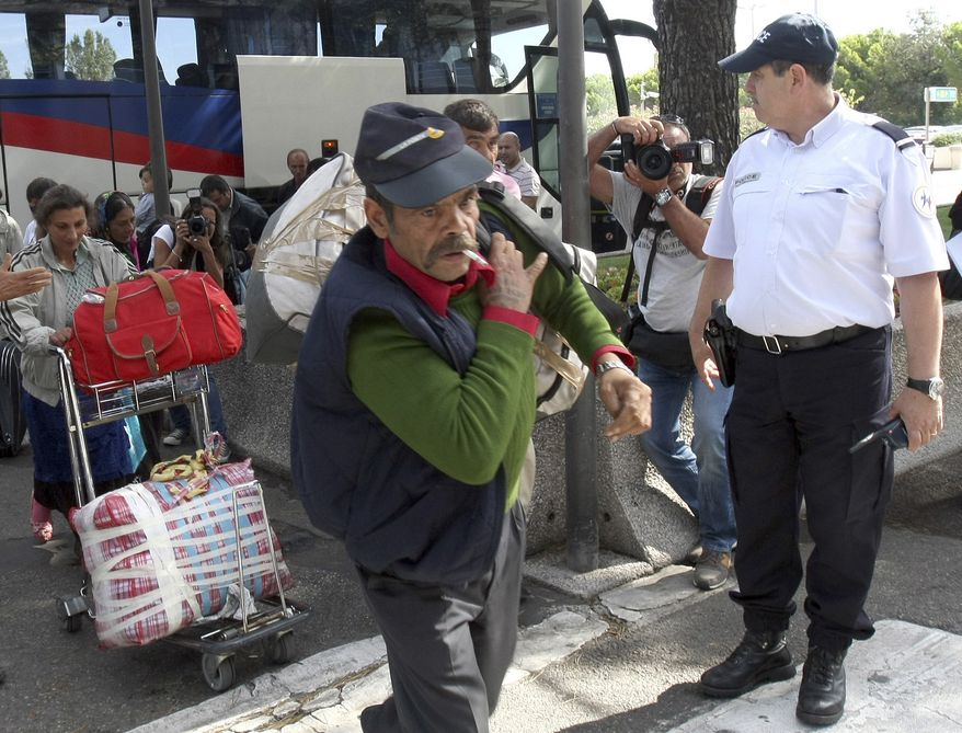 A police officer watches Roma also known as Gypsies, arrive at Marseille airport, southern France, before being expelled from France, Tuesday, Sept. 14, 2010. (AP Photo/Claude Paris)