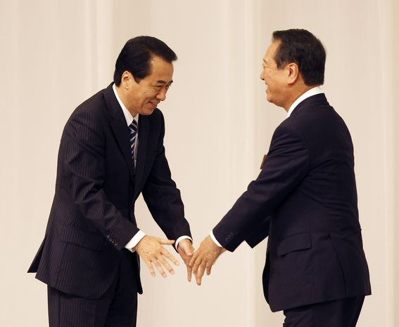 Japanese Prime Minister Naoto Kan, left, is congratulated by senior lawmaker Ichiro Ozawa as Mr. Kan was re-elected as president of the Democratic Party of Japan during their party convention in Tokyo, Tuesday, Sept. 14, 2010. (AP Photo/Junji Kurokawa)
