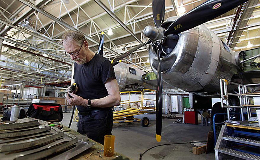 """In this photo taken July 14, 2010, Bill Wiesner, a retired Boeing machinist, prepares rivits for an engine panel on the Boeing B-29 Superfortress at right that he is helping restore at Boeing Co.'s historic """"Plant 2"""" in Seattle. After giving birth to some of the world's most significant aircraft, the outdated facility is scheduled to be torn down this fall, and a new home for the work of restoring the B-29 and other planes will need to be found. (AP Photo/Ted S. Warren)"""