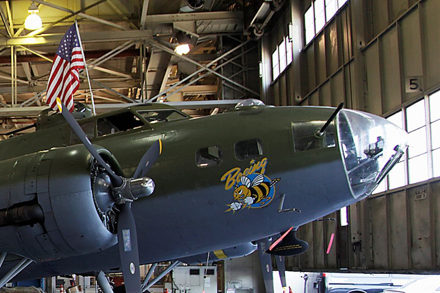 """In this photo taken July 14, 2010, a Boeing B-17F Flying Fortress that is undergoing restoration is parked in front of the massive doors of the Boeing Co.'s historic """"Plant 2,"""" in Seattle. After giving birth to some of the world's most significant aircraft, the outdated facility is scheduled to be torn down this fall. (AP Photo/Ted S. Warren)"""